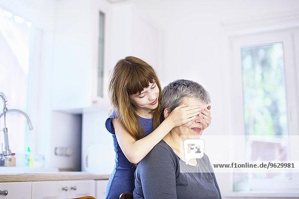 Mädchen  das Großmutters Augen am Küchentisch bedeckt