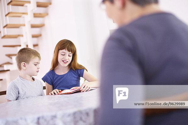 Großmutter beobachtet Enkelkinder beim Lesen am Küchentisch
