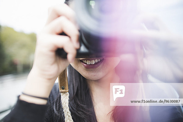 Young woman taking photographs  outdoors