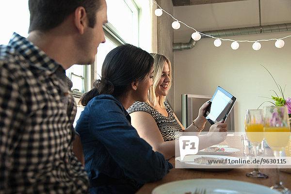 Gruppe von Freunden am Esstisch  mit Blick auf den digitalen Tablett-Bildschirm