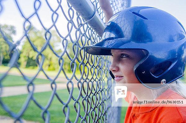 Junges Mädchen im Baseball-Kit  durch den Zaun schauend