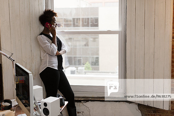 Woman using smartphone by window  home office