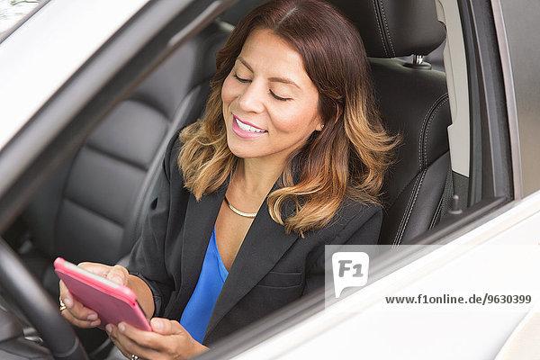 Geschäftsfrau mit Smartphone im Auto