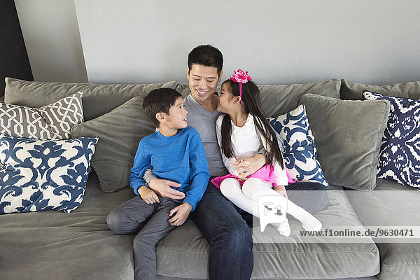 Mature man and two children sitting on living room sofa