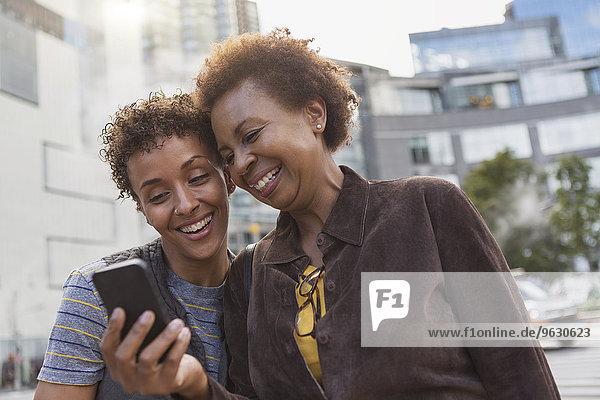 Zwei reife Freundinnen lachen über Smartphone-Texte auf der Straße