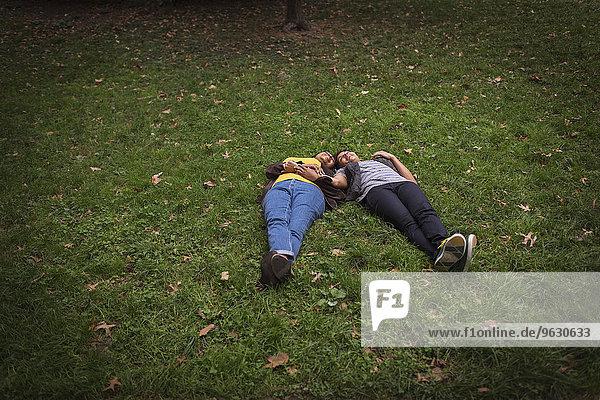 Zwei erwachsene Freundinnen liegen auf Parkgras Kopf an Kopf.