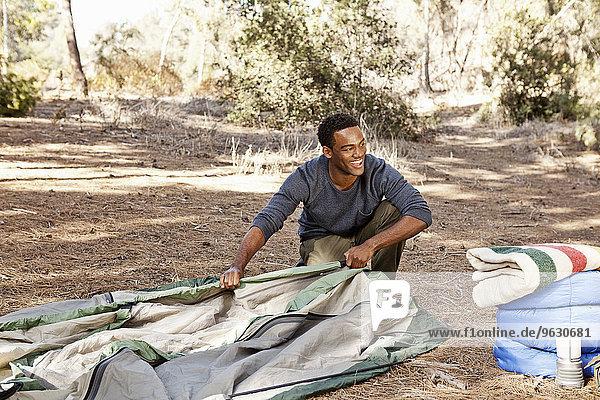Junger Mann kniend im Wald beim Aufbau des Zeltes