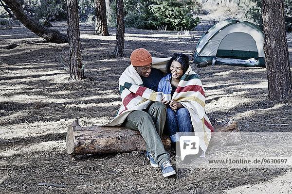 Junges Camping-Paar auf einem Baumstamm sitzend in Decke gehüllt