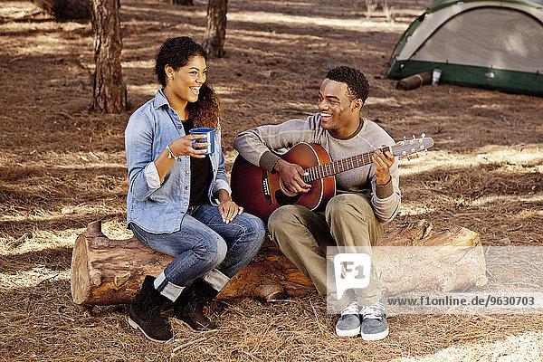 Junges Paar sitzt auf einem Waldblock und spielt Akustikgitarre.