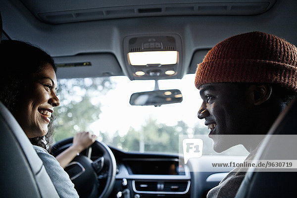 Junges Paar beim Plaudern auf dem Vordersitz des Autos