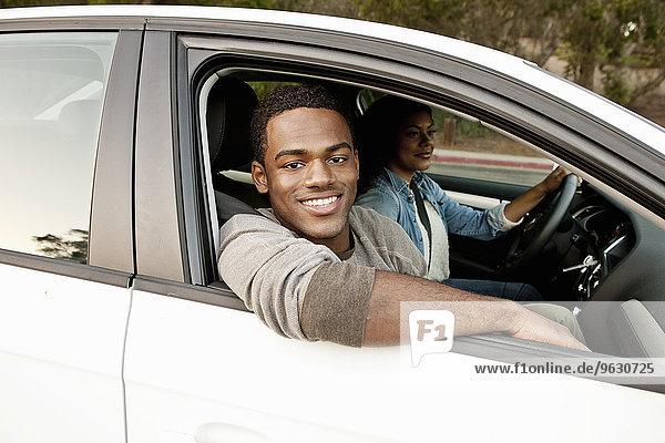 Porträt eines jungen Mannes  der aus dem Autofenster schaut.