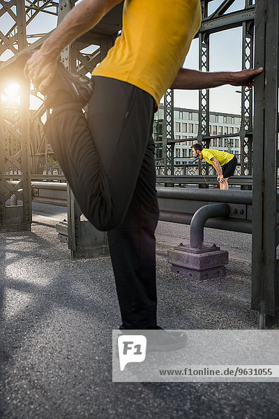 Mann streckt Bein auf Brücke  München  Bayern  Deutschland
