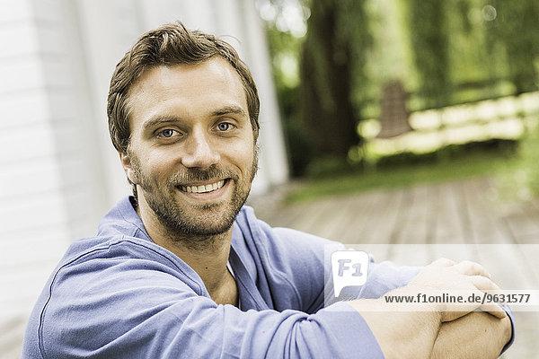 Nahaufnahme Porträt eines erwachsenen Mannes  der auf der Veranda sitzt.