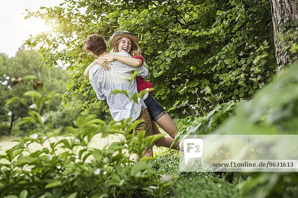 Junges Paar umarmt und lacht im Garten