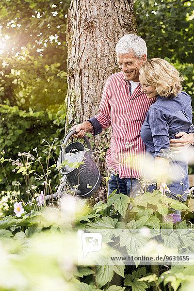 Mann und Frau beim Gießen von Pflanzen im Garten