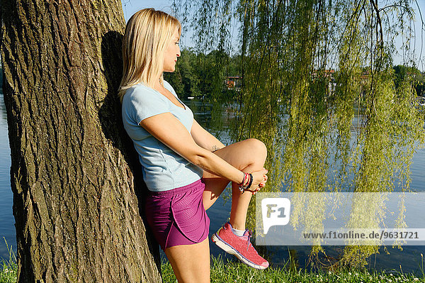 Mid adult woman stretching against tree