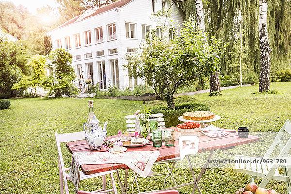 Tisch im Garten mit Teekanne  Teetassen  Kuchen und Erfrischungen