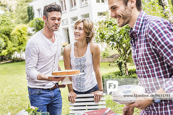 Gruppe von Freunden  die eine Gartenparty veranstalten  mittlerer Erwachsener mit Kuchen