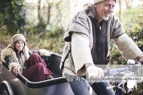 Ausgereiftes Hippie-Paar mit Dreirad und Anhänger auf der Landstraße