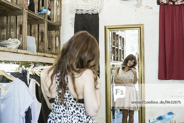 Mid Erwachsene Frau hält Kleid vor dem Spiegel in Vintage-Boutique