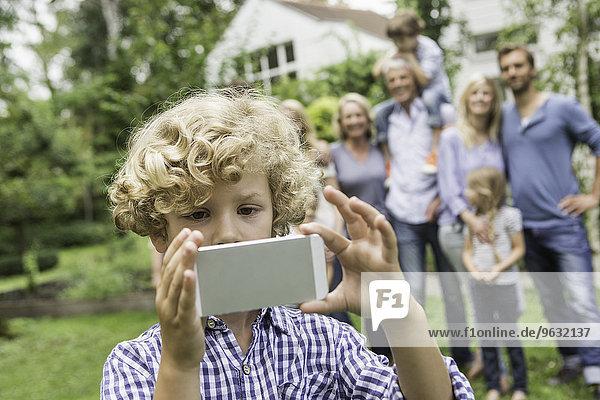 Junge mit Smartphone und Familie im Hintergrund