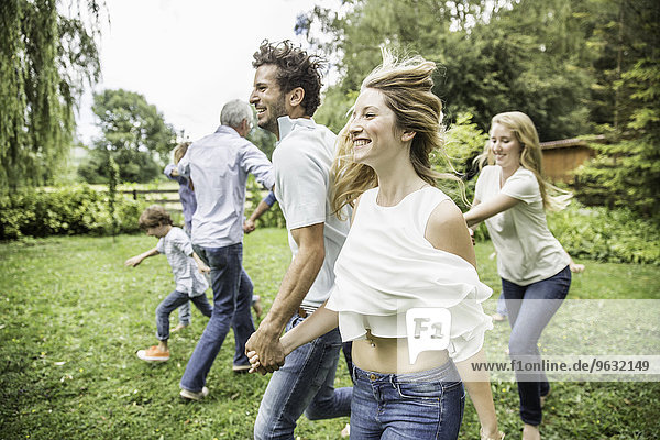 Young man and woman running in garden with family