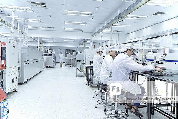 Mitarbeiter mit Mikroskopen in einer Fabrik  die sich auf die Herstellung von Funktionsschaltungen auf flexiblen Oberflächen spezialisiert hat.