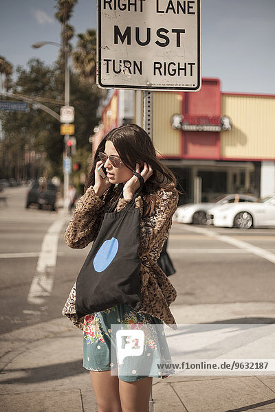 Young woman on corner of street  talking on mobile phone