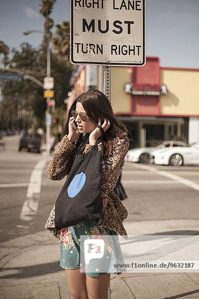 Junge Frau an der Straßenecke  die mit dem Handy telefoniert.