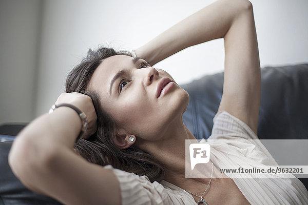 Junge Frau  die mit den Händen im Haar liegt.