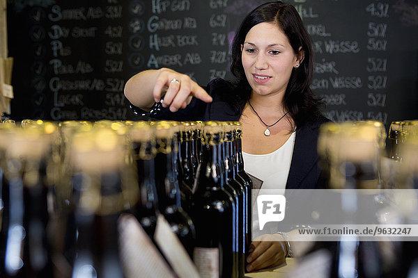 Frau beim Zählen von Weinflaschen im Geschäft