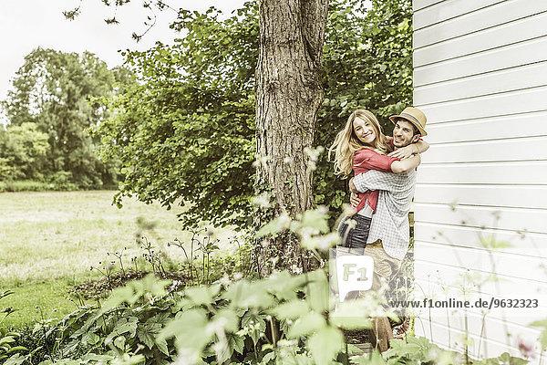 Junges Paar umarmt sich im Garten