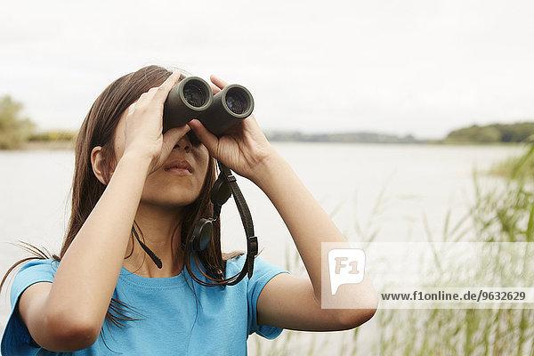 A young girl  a birdwatcher with binoculars.