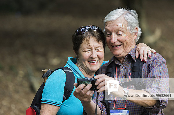 A mature couple looking at a digital camera  laughing.