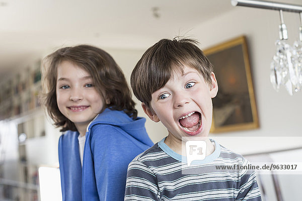 Boy making funny faces while girl in background