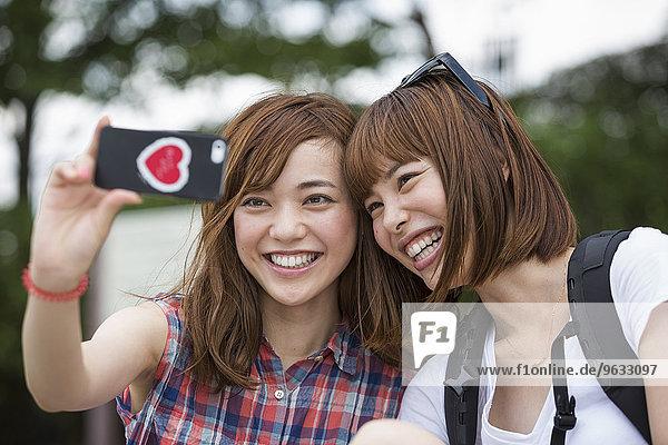 Two women  friends  taking a selfie in the park.