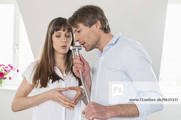 Couple pretend to sing and using water tab as microphone