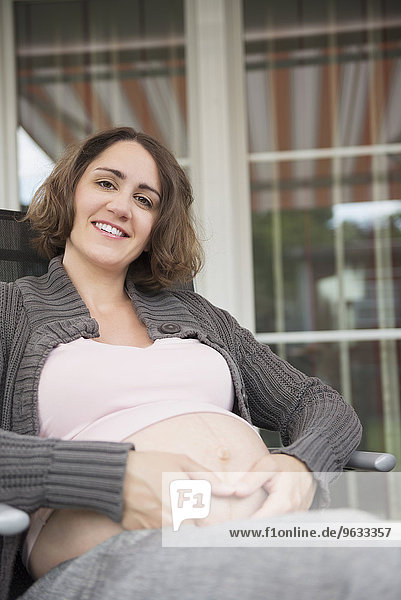Woman pregnant sitting terrace holding stomach
