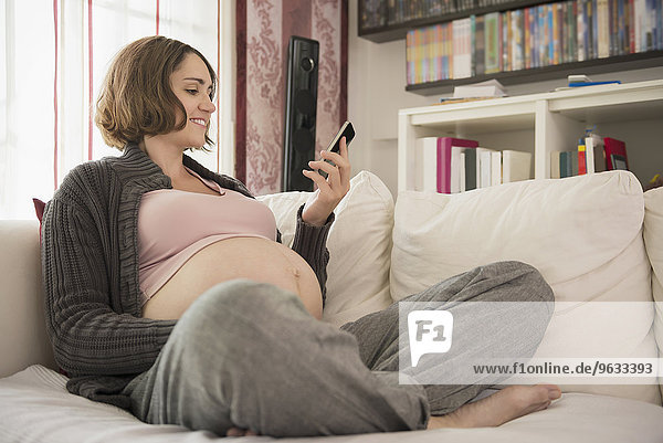 Smartphone woman sofa looking smiling happy