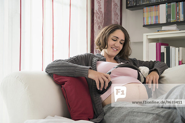 Holding smiling headphones pregnant woman happy