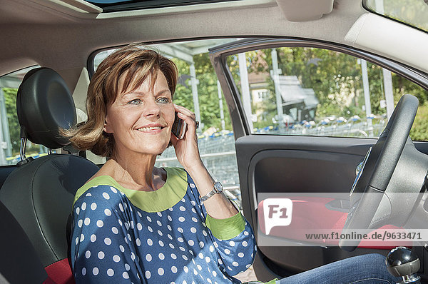 Senior woman sitting in car and talking on smart phone