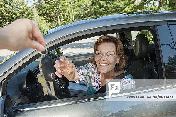 Senior woman receiving key for new car