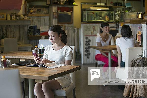 Handy sitzend Frau sehen Cafe Hintergrund Kurznachricht 2 Tisch