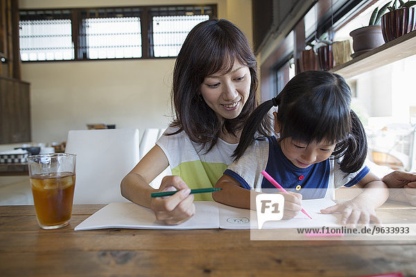 Mother and daughter sitting at a table  drawing with felt tip pens  smiling.
