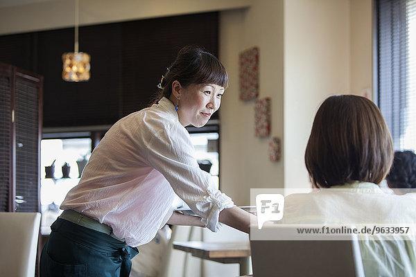 sitzend Frau geben Cafe Tisch Kellnerin