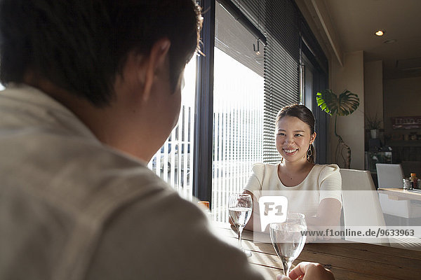 Woman and man sitting at a table in a cafe  smiling.