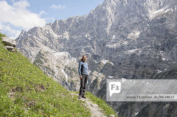 Woman alone mountain path trekking summer
