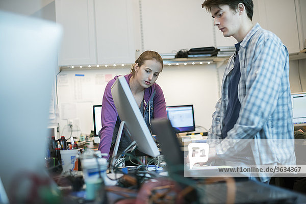 Two people  a man and woman standing at the counter in a computer repair shop.