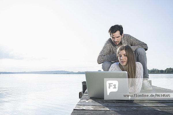 Lake sunset couple laptop computer working