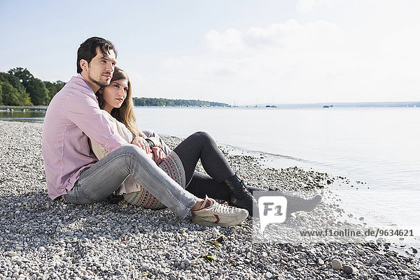 Loving young couple sitting shore lake